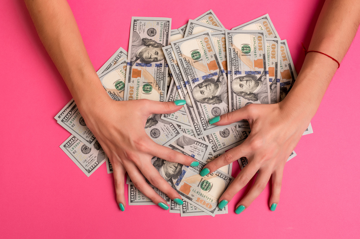 A woman is holding money in her hands. Pink background. Top view copy space
